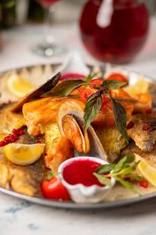Peixe grelhado assado e frutos do mar servidos com ervas, limão e molho de tomate vermelho.