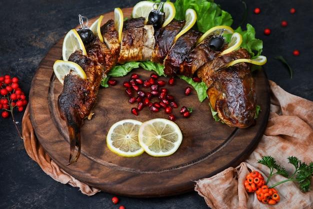 Peixe grelhado com ervas, frutas, limão