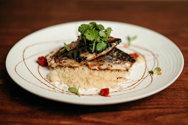 Peixe grelhado com mingau de cuscuz e salsa