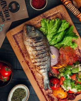 Peixe grelhado com polvilha salada de legumes, cebola e sumagre