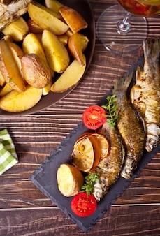 Peixe grelhado no prato com limão e vegetais