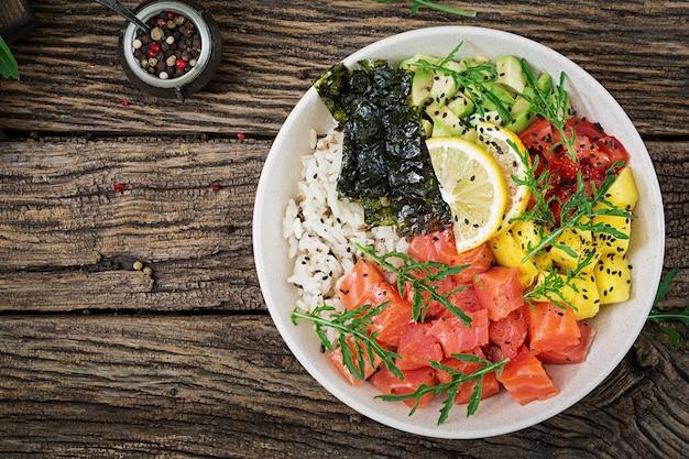 Peixe havaiano salmão picar tigela com arroz, abacate, manga, tomate, sementes de gergelim e algas. tigela de buda. dieta alimentar. vista do topo. configuração plana