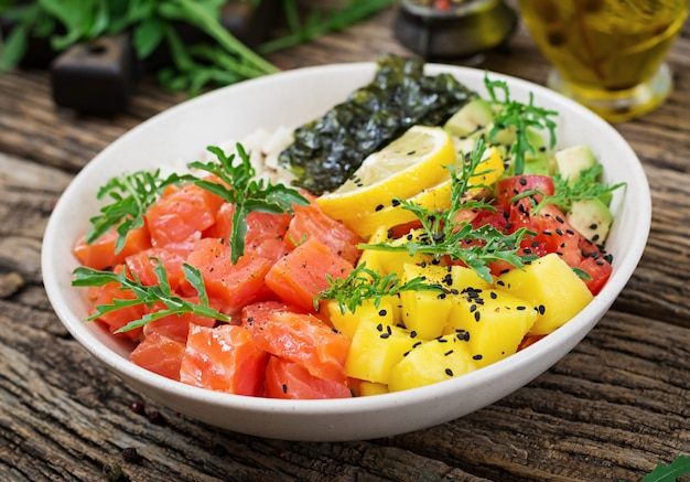 Peixe havaiano salmão picar tigela com arroz, abacate, manga, tomate, sementes de gergelim e algas. tigela de buda. dieta alimentar.