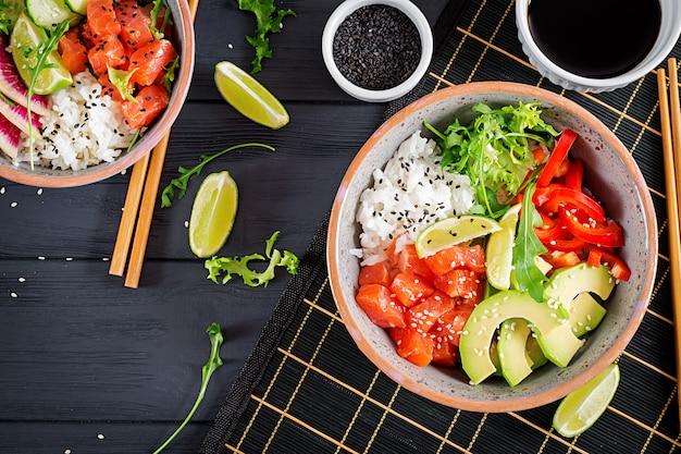 Peixe havaiano salmão picar tigela com arroz, abacate, pimentão, pepino, rabanete, sementes de gergelim e limão.