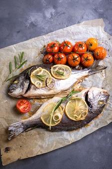 Peixe inteiro assado saboroso em papel manteiga. dourado assado com limão, cebola, ervas, tomate cereja, especiarias em fundo escuro e rústico.