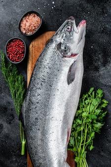 Peixe inteiro de salmão do mar cru cru em uma placa de madeira com ervas. fundo preto. vista do topo.