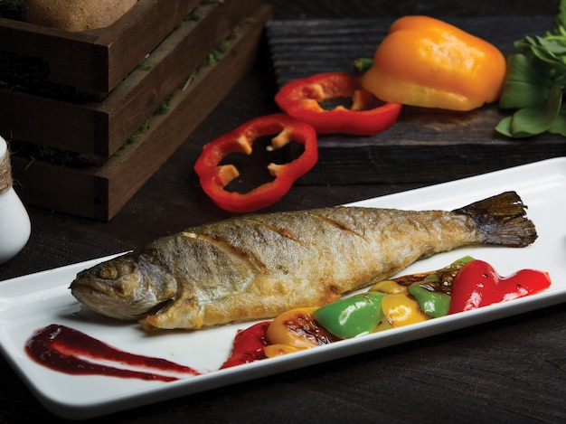 Peixe inteiro grelhado servido com pimentão grelhado