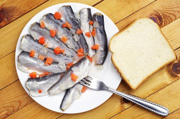 Peixe marinado em um prato com fundo de madeira. vista do topo