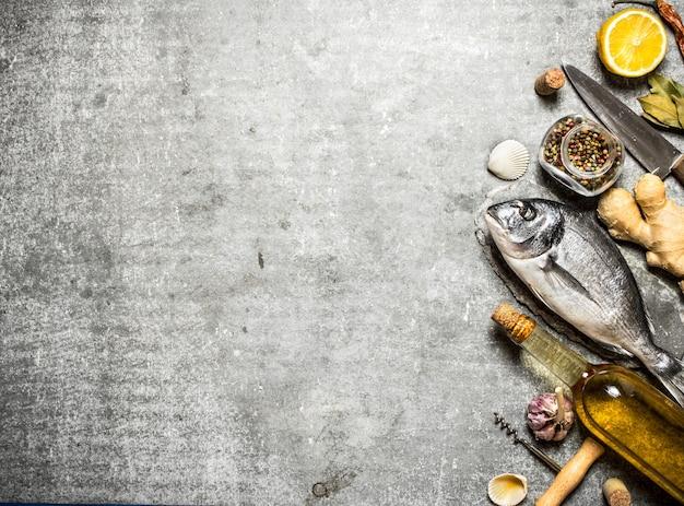 Peixe marinho com vinho e uma variedade de especiarias e ervas no concreto
