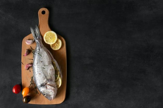 Peixe mediterrâneo - dorado e legumes numa tábua. vista do topo.