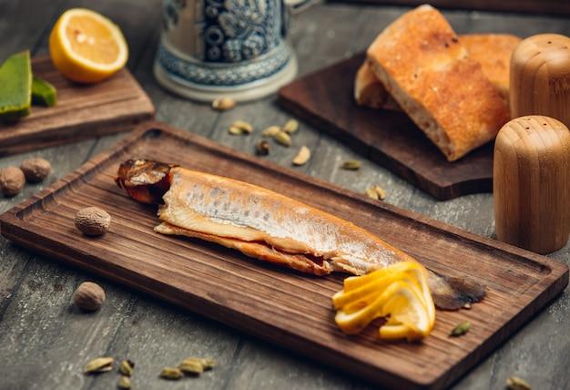 Peixe na placa de madeira com limão