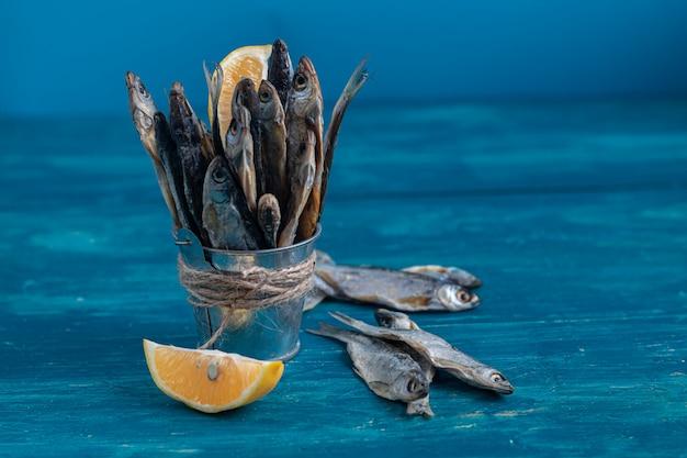 Peixe pequeno e salgado. perto das fatias de limão. peixe do mar.