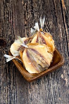 Peixe pequeno eviscerado e seco com sal, peixes pequenos secos e abatidos em uma mesa de madeira