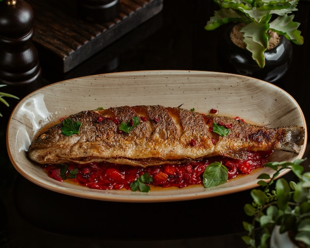 Peixe refogado em molho de romã e servido em prato granado
