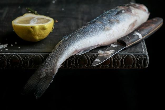 Peixe robalo cru fresco na mesa de madeira preta
