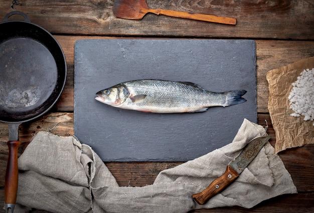 Peixe robalo fresco inteiro em um quadro negro