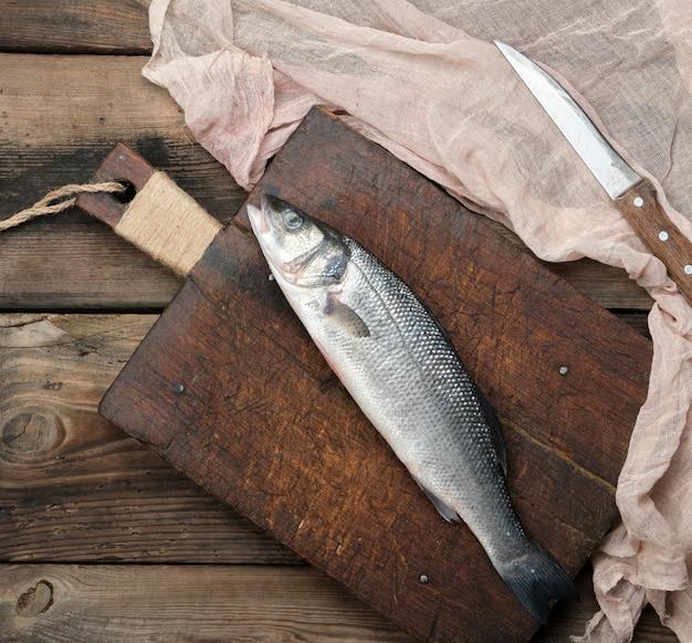 Peixe robalo inteiro fresco na tábua marrom