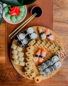 Peixe rola uma refeição picante salgada saborosa vista superior, juntamente com molho preto na superfície de madeira marrom