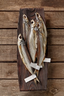 Peixe-sabre salgado e seco ao ar com rótulos nas caudas em um prato de madeira