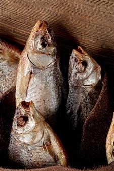 Peixe salgado e seco ao ar envolto em couro genuíno com fundo de madeira
