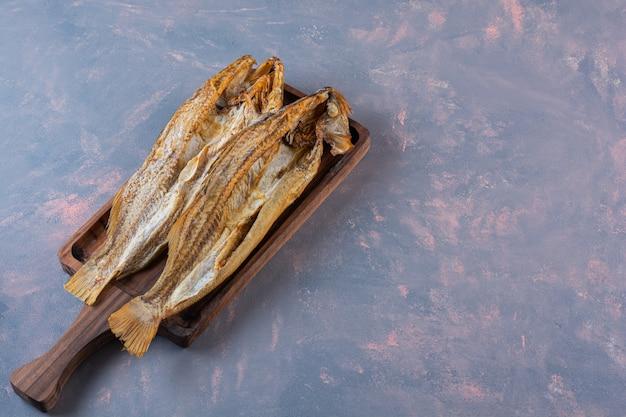 Peixe salgado no tabuleiro, na superfície de mármore