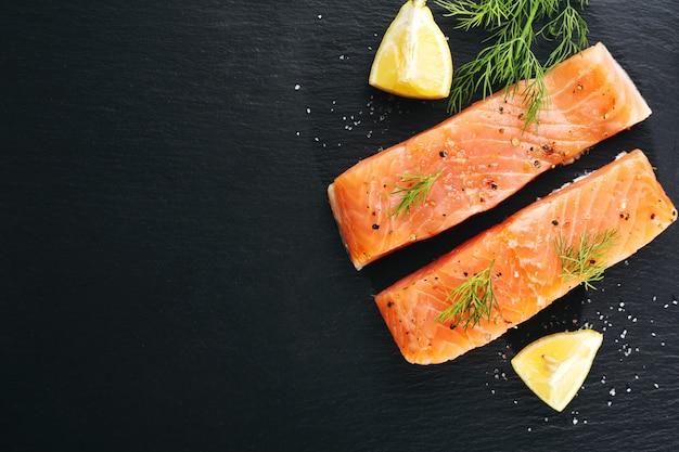 Peixe salmão cru na ardósia preta