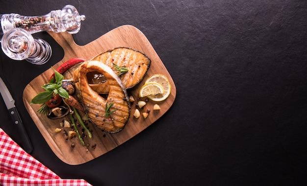 Peixe salmão grelhado com tempero e vários legumes na tábua em pedra preta