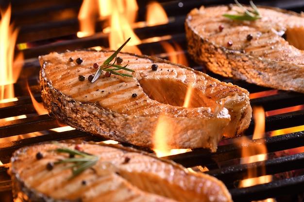 Peixe salmão grelhado com vários legumes na grelha flamejante