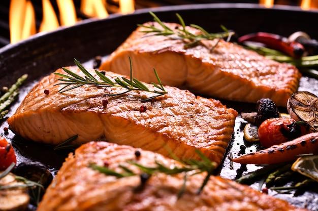 Peixe salmão grelhado com vários legumes na panela na grelha flamejante