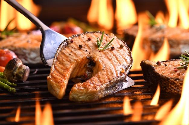 Peixe salmão grelhado com vários vegetais na grelha flamejante
