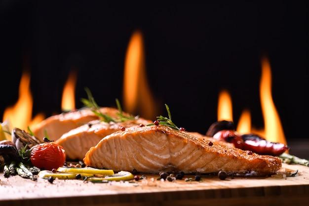 Peixe salmão grelhado e vários legumes na mesa de madeira