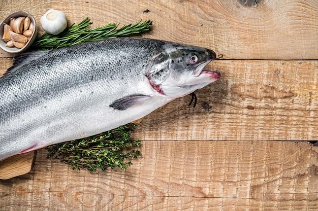 Peixe salmão marinho cru em uma mesa de cozinha de madeira com ervas. fundo de madeira.