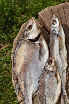 Peixe seco ao ar salgado deitado em um toco de madeira ao ar livre