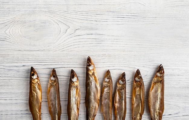 Peixe seco com cheiro é um lanche ideal para cerveja em um fundo de madeira ou quadro branco.
