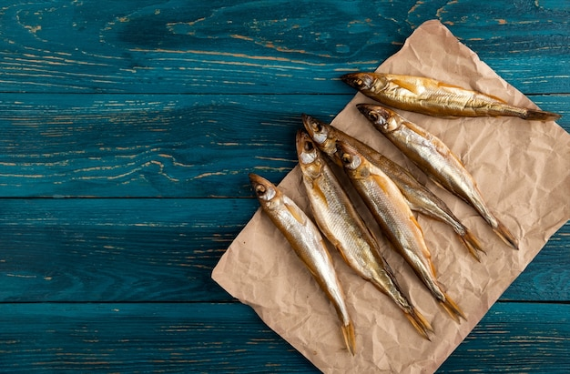Peixe seco com cheiro é um petisco ideal para cerveja. encontra-se em papel kraft velho, sobre um fundo de madeira azul escuro de placas.