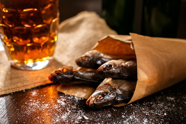Peixe seco e vintage copo de cerveja em uma superfície preta