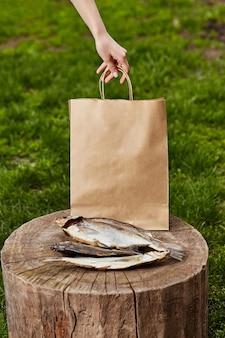 Peixe seco no toco de madeira no fundo com uma mão feminina segurando um saco de papel
