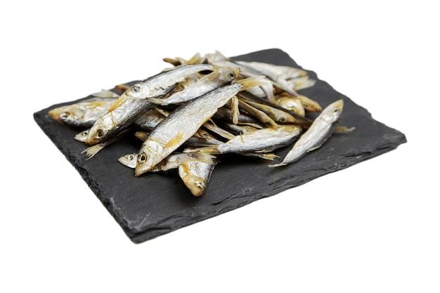 Peixe seco pequeno na placa de ardósia preta, isolado no fundo branco. petisco de cerveja.