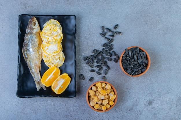 Peixe seco salgado, batatas fritas e limão fatiado em uma travessa ao lado de uma tigela de grão de bico e sementes, na superfície de mármore.