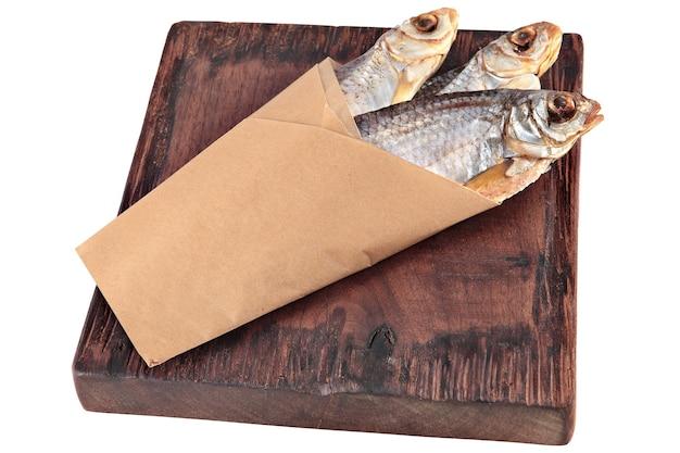 Peixe seco salgado, embrulho de três baratas secas ao sol em papel vegetal a bordo de madeira manchada de vermelho escuro, petisco de cerveja.