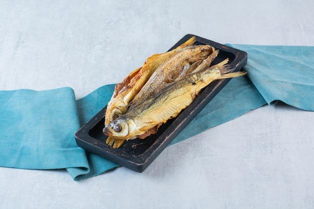 Peixe seco salgado isolado em uma placa de madeira.