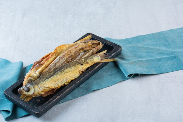 Peixe seco salgado isolado em uma placa de madeira