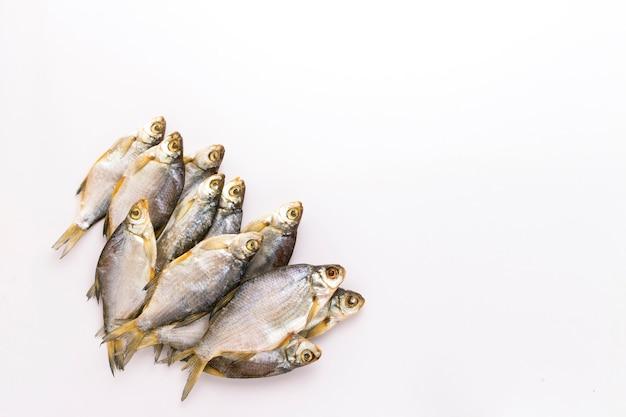 Peixe seco sobre um fundo branco. vista plana leiga, superior.