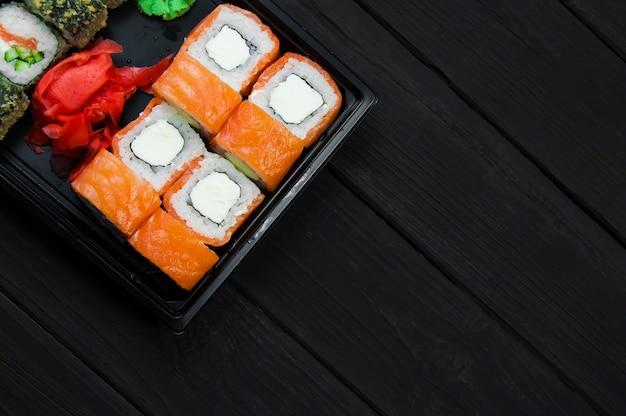 Peixe sushi com molho e gengibre em uma mesa de madeira preta, vista de cima