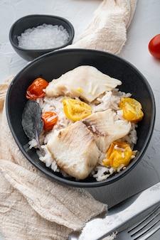 Peixe tilápia com arroz basmati e tomate cereja, em uma tigela, na mesa branca
