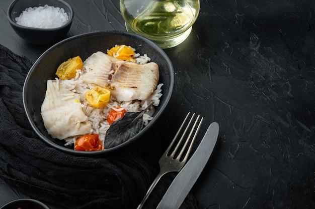 Peixe tilápia com arroz basmati e tomate cereja, em uma tigela, na mesa preta