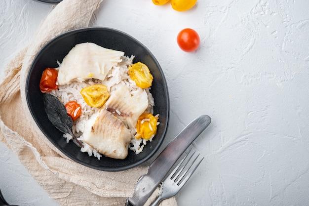 Peixe tilápia com arroz basmati e tomate cereja, em uma tigela, sobre fundo branco, vista superior com espaço de cópia para o texto