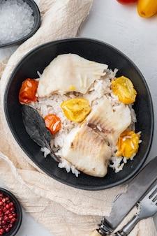 Peixe tilápia com arroz basmati e tomate cereja, na tigela, na mesa branca, vista superior