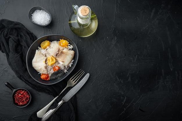 Peixe tilápia com arroz basmati e tomate cereja, na tigela, na mesa preta, vista de cima