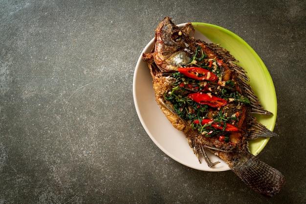 Peixe tilápia frito com molho de pimenta e alho com manjericão no topo